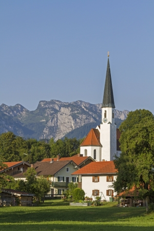 The idyllic village church of Arzbach with Benediktenwand Stock Photo