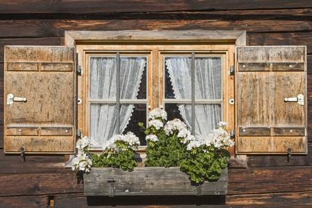 Fenster mit Fensterläden und Blumenschmuck auf alten Alm