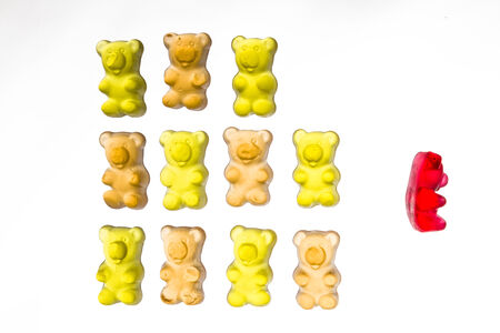 Symbol Image with gummy bears  mobbed by colleagues