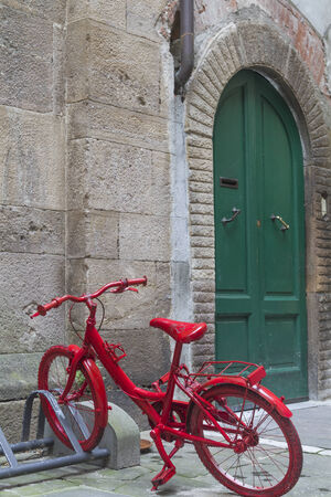 Flame red lacquered bicycle in front of a green door photo