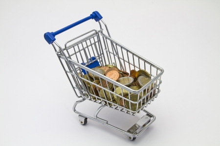 Miniature shopping cart with many Euro and Cent coins photo