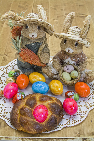 Easter Bunny pair  with colored eggs and Easter cake photo