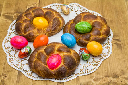 Easter baking - yeast pastries decorated with colored easter egg photo