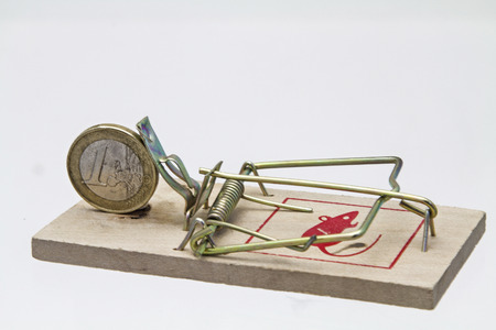 Primitive and powerful - Mousetrap and coin  on white background photo
