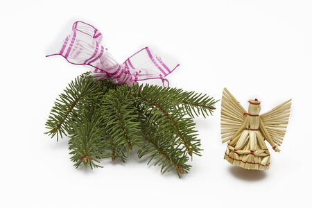 tinkering: Fir tree branch with red ribbon and straw angel Stock Photo