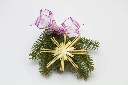 straw twig: Fir tree branch with red ribbon and straw star Stock Photo
