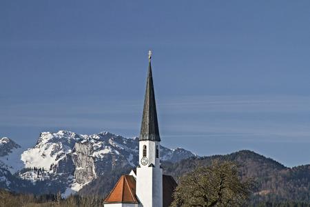 village church in Arzbach and snowcovered  Benediktenwand