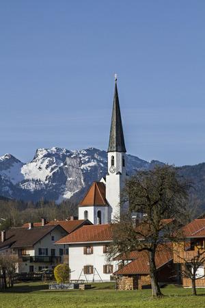 The idyllic village church of Arzbach with snowy Benediktenwand in Early Spring