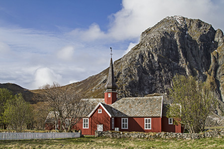 The red wooden church of Flakstad in Lofoten was built against a magnificent mountain scenery