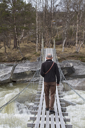 exceeding: he exceeding of a wild river on a rickety suspension bridge requires a lot of courage Stock Photo