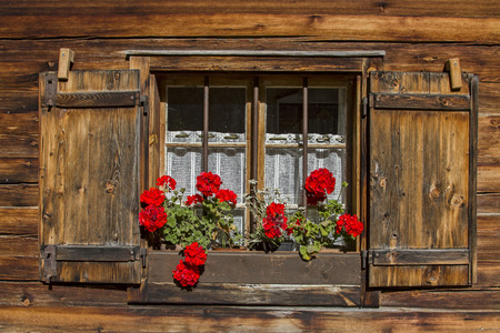 Window with shutters and flower decoration on old hut Standard-Bild