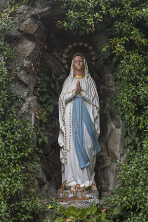 devout: Statue of Mary in a grotto, a center of attraction for devout visitors Stock Photo