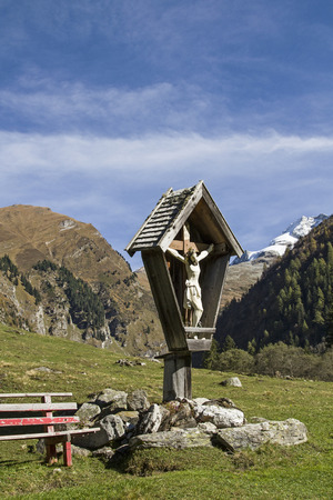 piety: Idyllic wayside cross in the Vals Valley in Tyrol with the summit of Olperer Stock Photo