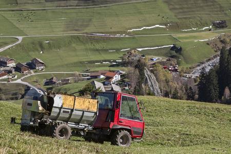 schweiz: Farmer scatters his manure on a steep mountain meadow in Switzerlandstreut seinen Stallmist auf ein steile Bergwiese in der Schweiz Stock Photo