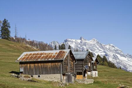 prato montagna: capanne su un prato di montagna nella valle di Medel in Svizzera Archivio Fotografico