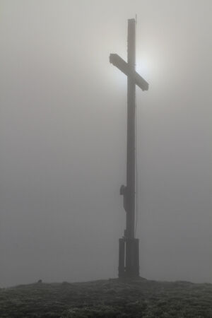 diffuse: Summit cross of Heigl head in the Bavarian Alps with diffuse translucent through the fog sun