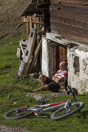 strenuous: Mountain Biker rests on the wall of a mountain lodge after a strenuous tour