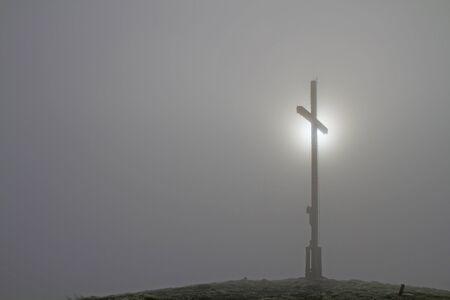 dreary: Summit cross of Heigl head in the Bavarian Alps with diffuse translucent through the fog sun