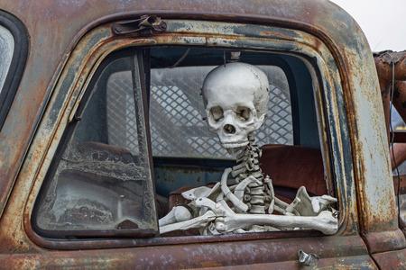 skelett mensch: Skelett am Steuer eines alten Schrottautos