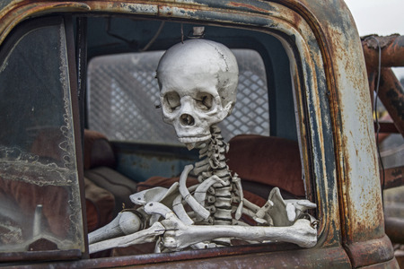 oldie: skeleton at the wheel of an old junk cars
