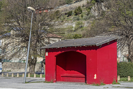 roofed house: Red bus shelter offers waiting passengers protection from the weather