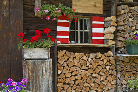 den: Fenster mit Fensterläden und Blumenschmuck an alter Almhütte im Karwendelgebirge