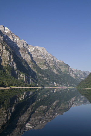 incurred: The Lake Klöntal is incurred by a landslide lake in the canton of Glarus in Switzerland Stock Photo