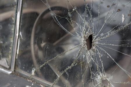Car window after a raid has a  bullet hole