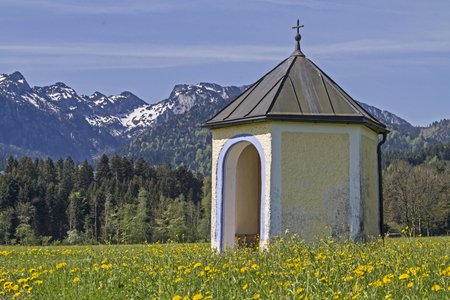 piety: Small meadows chapel before the mountain group of Benediktenwand Stock Photo