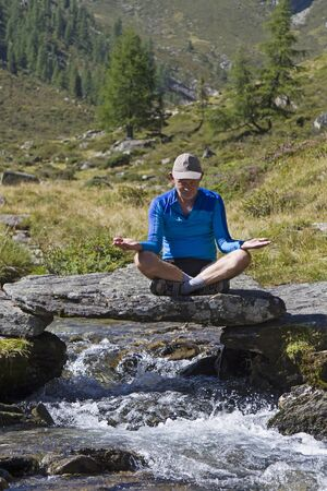 torrent: Man meditating on a small stone bridge over a mountain torrent Stock Photo
