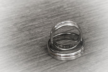 vows: Monochrome illustration of two wedding rings on wooden background Stock Photo