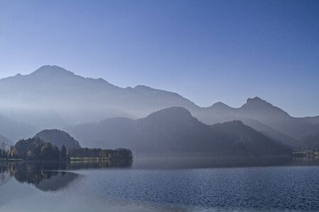 sentiment: Haze sentiment of Kochelsee lake with the silhouette of the house garden Stock Photo