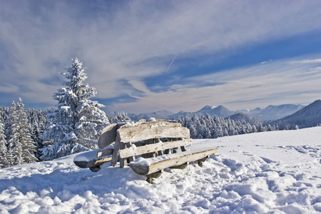winter wood: Rest bench on a small secondary summit in Benediktenwand area in winter Stock Photo