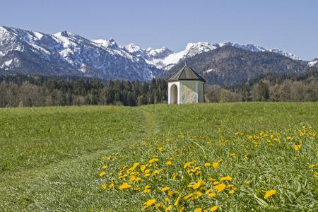 frhling: Kleine Wiesenkapelle vor der Gebirgsgruppe der Benediktenwand Stock Photo