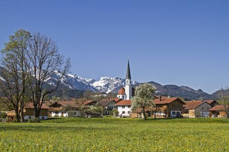 The idyllic village church of Arzbach with snowy Benediktenwand in spring