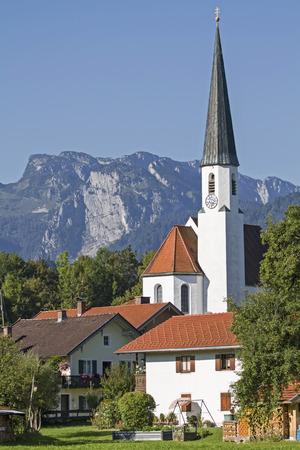 The idyllic village church of Arzbach with Benediktenwand in summer