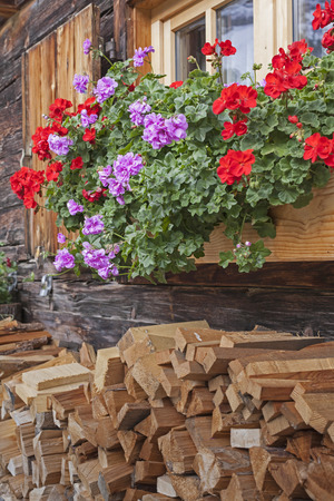 mountain hut: Window with window shutters and flower decoration at an old mountain hut Stock Photo