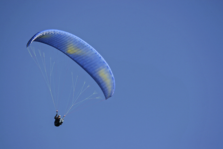 Paraglider with blue umbrella in front of cloudless sky Zdjęcie Seryjne