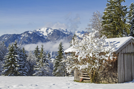 benedict: Winter in Isarwinkel - hay hut in front of the snow-capped mountains of the Benedictine Wall Stock Photo