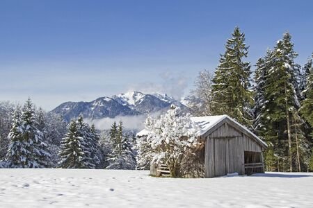 Winter in Isarwinkel - hay hut in front of the snow-capped mountains of the Benedictine Wall Stock Photo