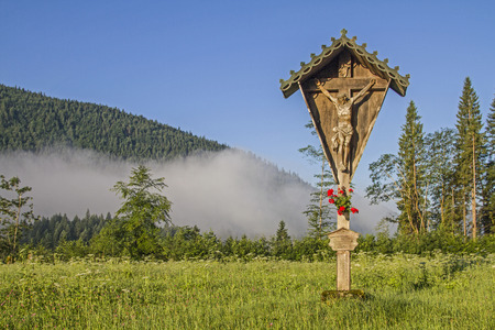 Idyllic cross on a flower meadow in the valley of the Jachenau with floor mist