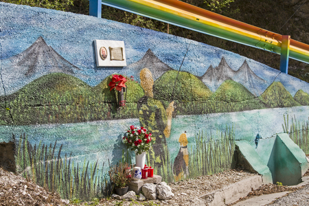 A colorful picture of a tragic occasion on a concrete wall - memorial for the victim of a traffic accident Фото со стока