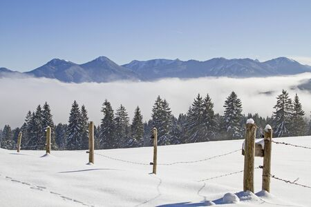 Fog in the valley and sun on the mountains - Winter idyll in the Isarwinkel near Bad Toelz Stock Photo