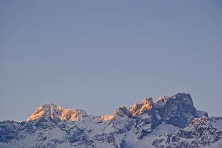 The first rays of the sun illuminate the mountain peaks of the snowy Karwendel mountains Standard-Bild - 93786045