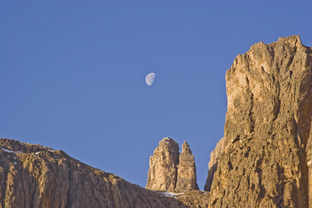 Despite the advanced morning hour, the moon is clearly visible over the rock towers of the Sella group