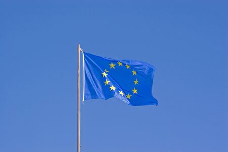 European Union flag flutters in front of blue sky in the wind Imagens