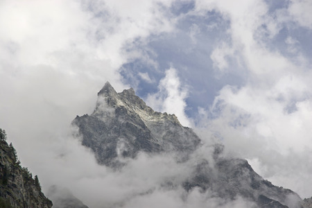 Mighty three-thousanders seen  through  bad weather clouds Standard-Bild - 98339657