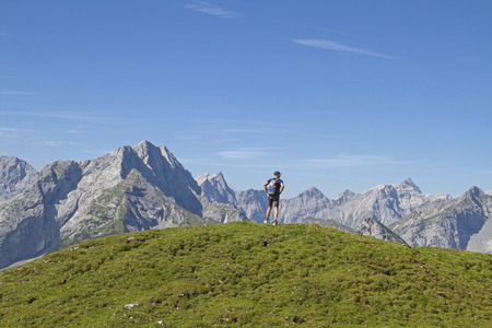 Mountaineer has reached the highest point of the Satteljoch and enjoy the view Standard-Bild - 109522161
