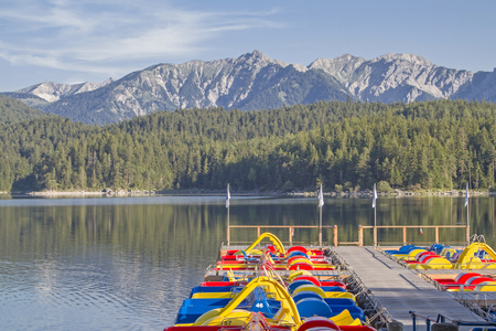 Colorful pedal boats invite the countless tourists to a sporty pleasure ride on the Eibsee