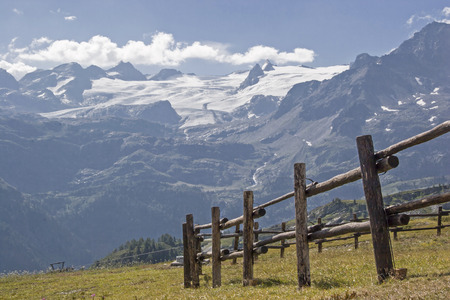 Pasture fence on an alpine meadow in the glacier-rich mountains of the Savoy Alps Standard-Bild - 111340009